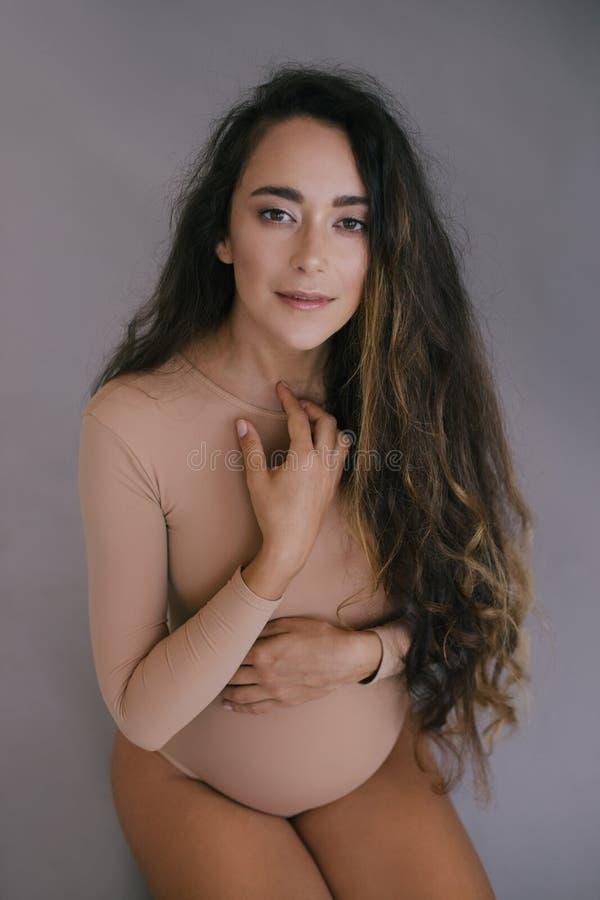 Bella donna incinta con capelli lunghi su fondo grigio fotografia stock
