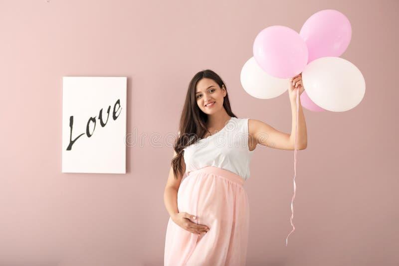 Bella donna incinta con gli aerostati sul fondo di colore fotografie stock libere da diritti