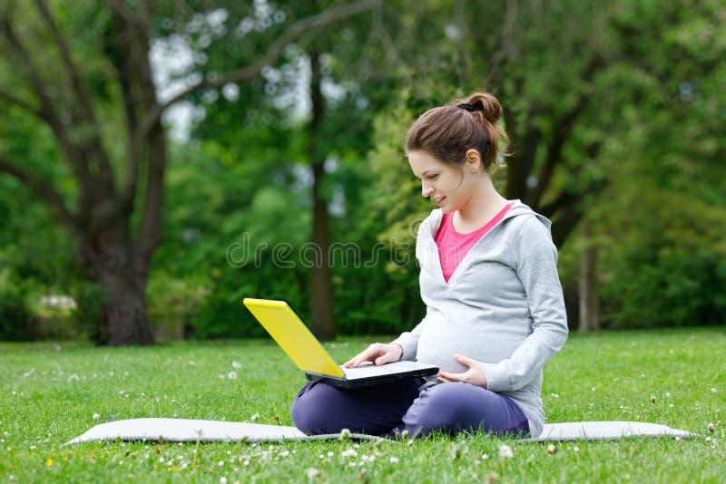 Bella donna incinta con il computer portatile fotografie stock libere da diritti