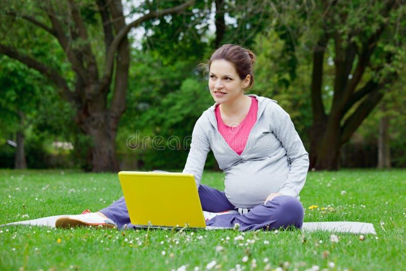 Bella donna incinta con il computer portatile fotografia stock
