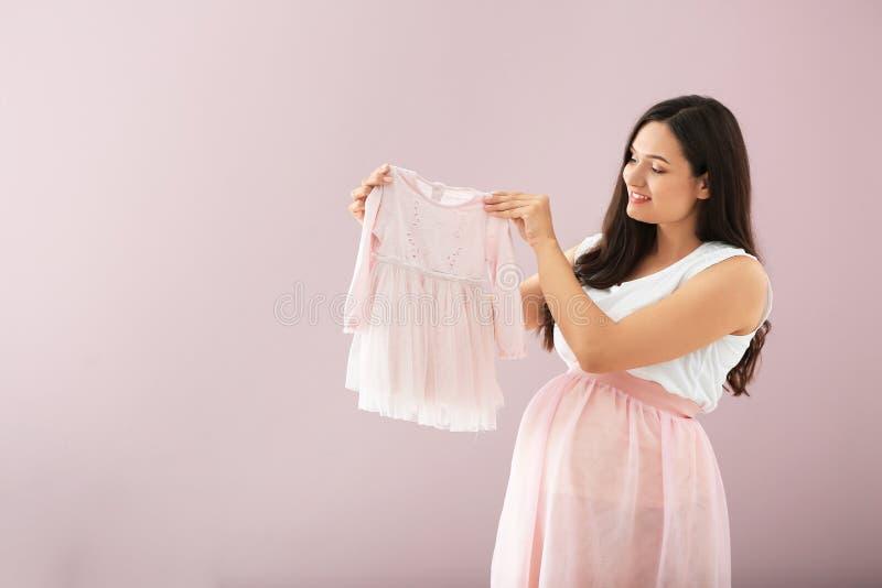 Bella donna incinta con il vestito dal bambino sul fondo di colore fotografia stock libera da diritti