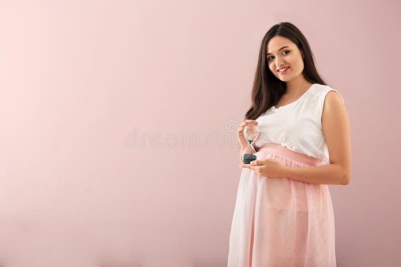 Bella donna incinta con la clessidra sul fondo di colore immagini stock libere da diritti