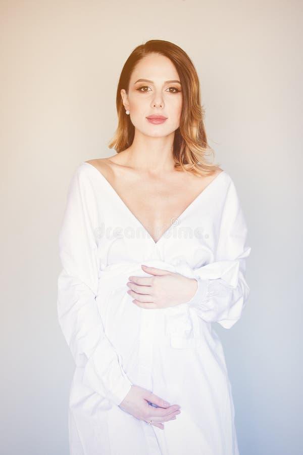 Bella donna incinta della testarossa in vestito bianco fotografie stock