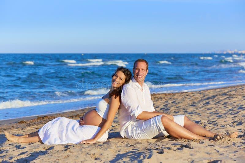 Bella donna incinta delle coppie nella spiaggia fotografie stock