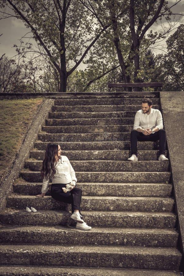 Bella donna incinta e suo il marito che si siedono sull'le scale di pietra fotografie stock libere da diritti