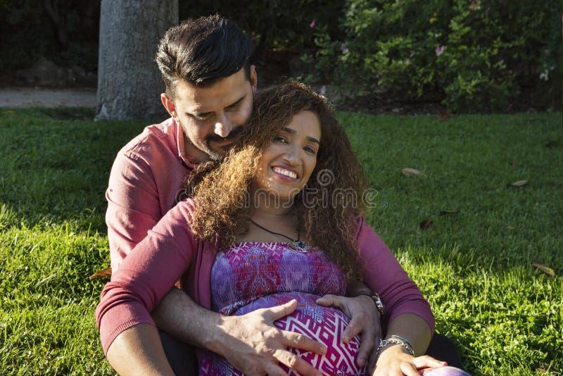 Bella donna incinta ed il suo marito nel parco fotografia stock libera da diritti