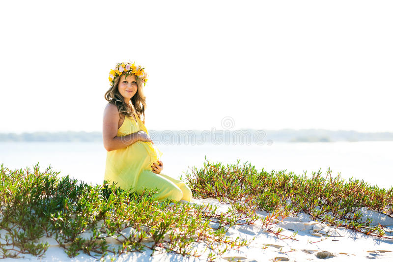 Bella donna incinta sorridente con i fiori che si siedono su una spiaggia immagine stock