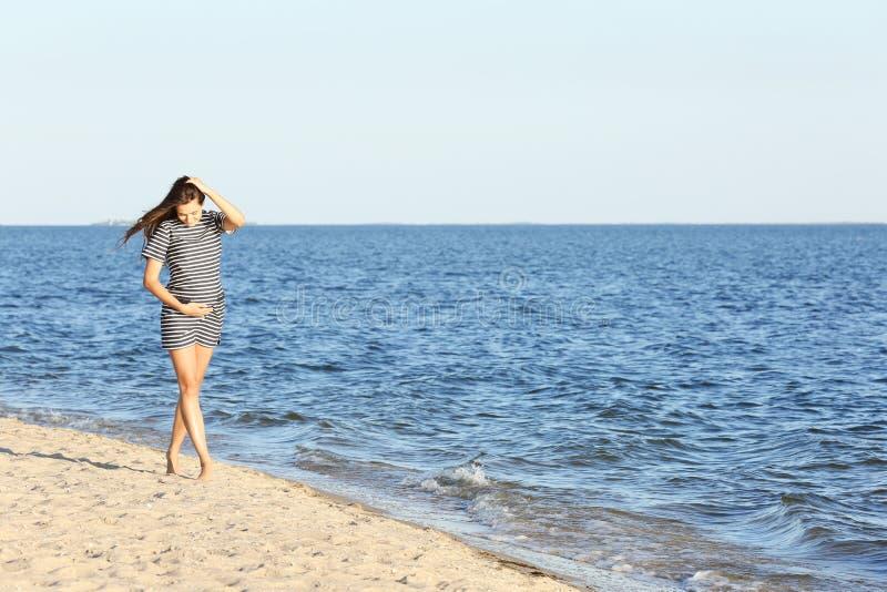 Bella donna incinta in vestito a strisce che cammina sulla spiaggia immagine stock