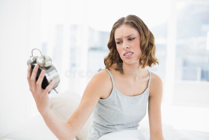 Bella donna infastidita che tiene una sveglia che lo esamina che si siede sul suo letto immagini stock libere da diritti