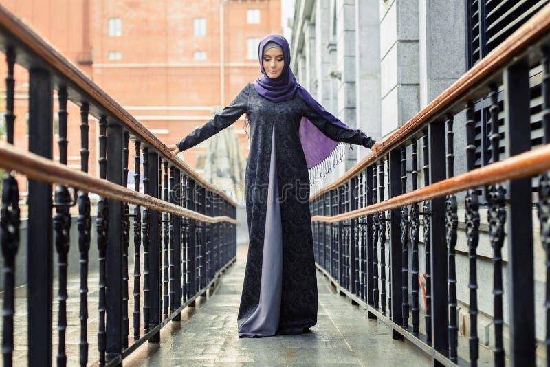 Bella donna islamica in un vestito musulmano che sta su una via europea fotografia stock libera da diritti