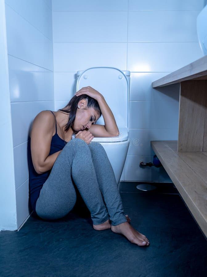 Bella donna latina che si siede nel bagno che soffre dalla bulimia di anoressia che ritiene triste e colpevole disperati nei diso fotografia stock libera da diritti