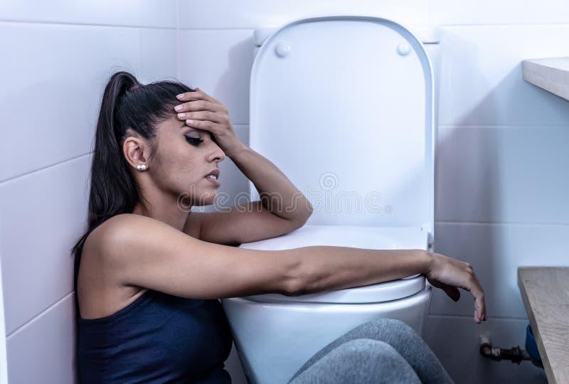 Bella donna latina che si siede nel bagno che soffre dalla bulimia di anoressia che ritiene triste e colpevole disperati nei diso fotografie stock libere da diritti