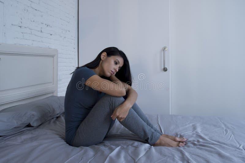 Bella donna latina triste e depressa che si siede sul letto a casa f fotografia stock libera da diritti