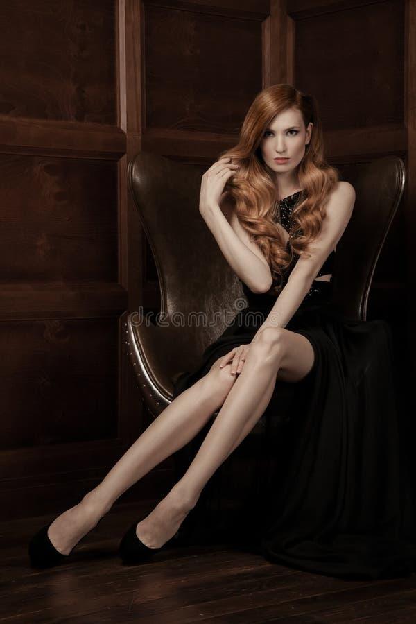 Bella donna lussuosa che si siede su una sedia d'annata di cuoio fotografia stock
