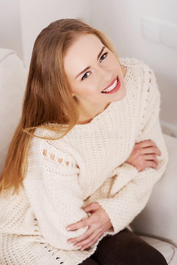 Bella donna in maglione luminoso che si siede su uno strato. fotografia stock libera da diritti