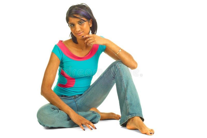 Bella donna marrone che si siede sul pavimento fotografia stock libera da diritti