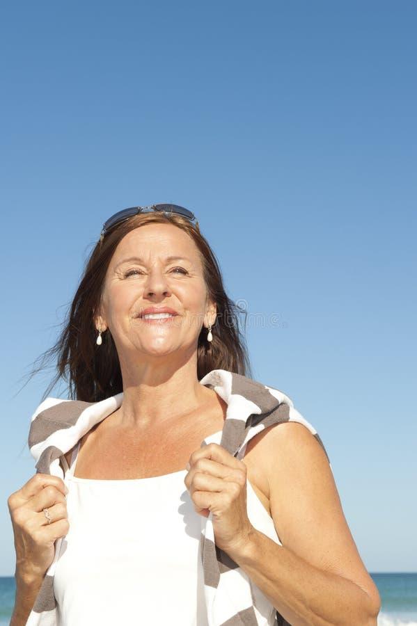 Bella donna matura che gode della pensione alla spiaggia - Alla colorazione della spiaggia ...