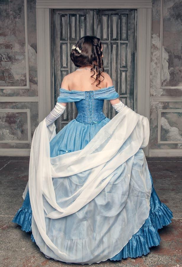 Bella donna medievale in vestito blu, posteriore immagini stock
