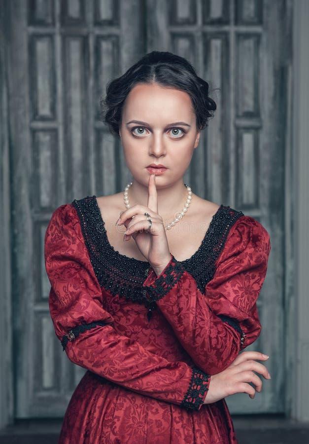 Bella donna medievale in vestito rosso che fa gesto di silenzio immagine stock