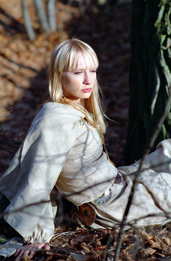 Bella donna medioevale che si siede nella foresta immagini stock