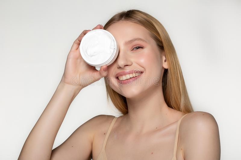 Bella donna mezzo nuda sorridente con capelli biondi nascondere gli occhi uno con il tubo della crema isolato sopra fondo grigio  fotografie stock