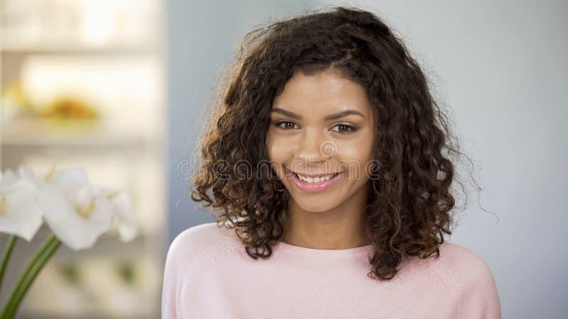 Bella donna multirazziale che sorride alla macchina fotografica, alla salute ed alla femminilità, positività fotografie stock libere da diritti