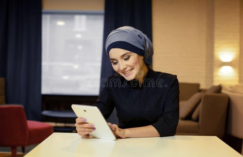 Bella donna musulmana con la compressa elettronica fotografia stock
