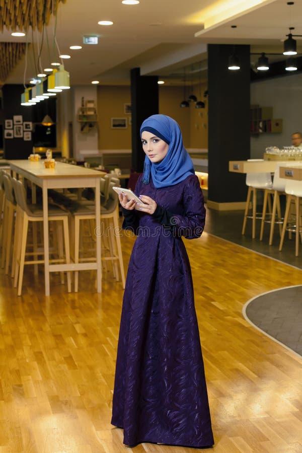 Bella donna musulmana con la compressa elettronica in sue mani, nell'ingresso dell'hotel fotografia stock