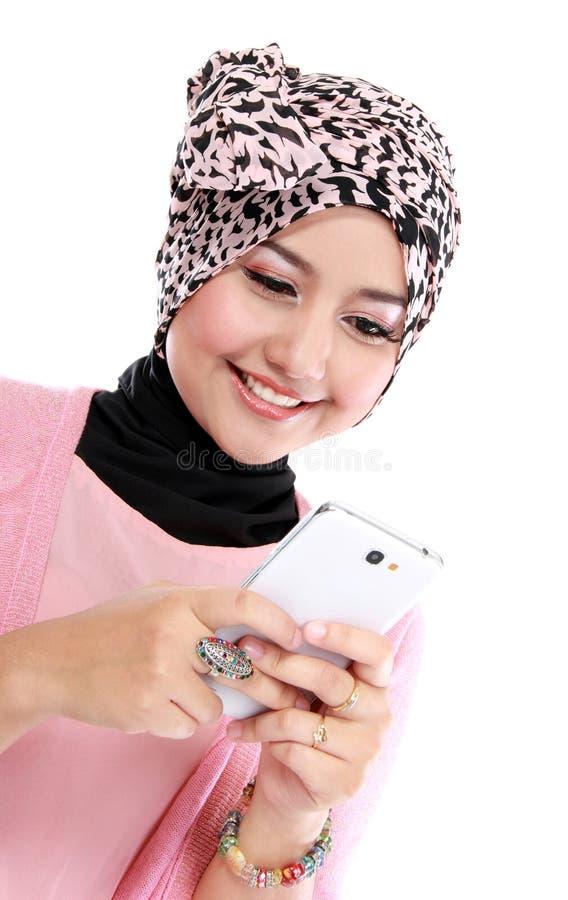 Bella donna musulmana sorridente che manda un sms con il suo smartphone fotografie stock libere da diritti