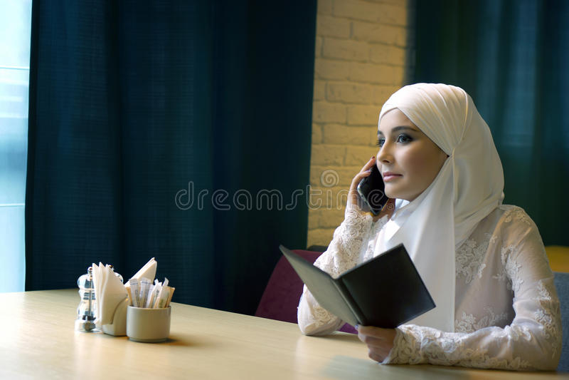 Bella donna musulmana in un vestito da sposa bianco che si siede in caffè e che parla sul telefono fotografia stock libera da diritti