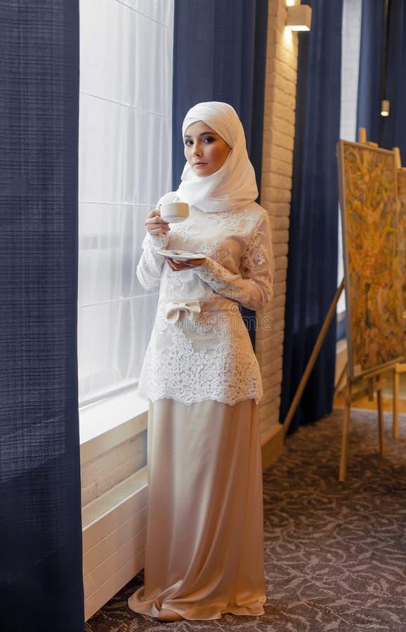 Bella donna musulmana in un vestito da sposa bianco che sta alla finestra immagini stock libere da diritti