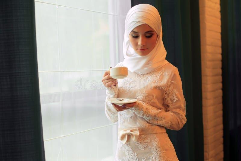 Bella donna musulmana in un vestito da sposa bianco con una tazza di tè in sue mani fotografia stock