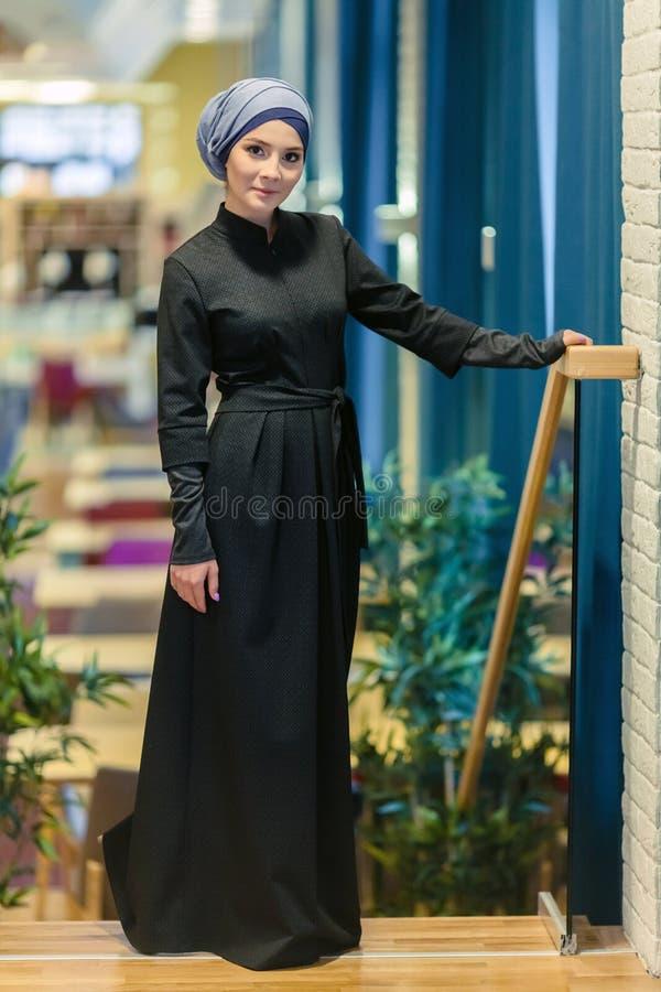 Bella donna musulmana in un vestito orientale moderno che sta nell'atrio del ristorante immagini stock libere da diritti