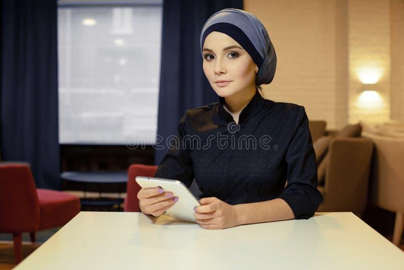 Bella donna musulmana in vestiti islamici che si siedono ad una tavola con una compressa elettronica in sue mani immagine stock