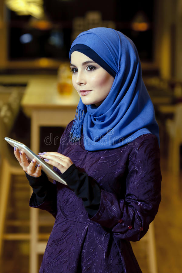 Bella donna musulmana in vestiti tradizionali con la compressa elettronica in mani fotografie stock