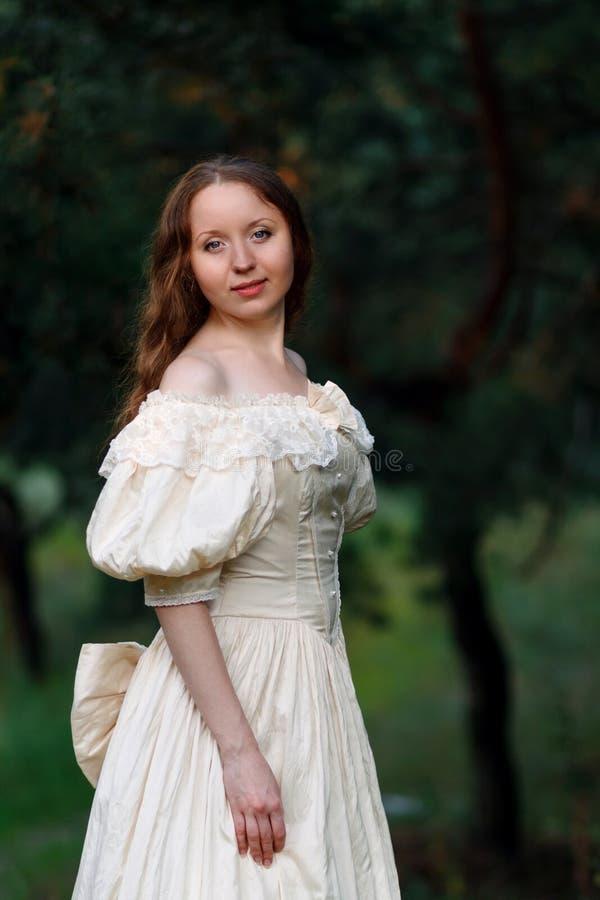 Bella donna nel beige d'annata del vestito Ragazza sveglia in vestito lungo che cammina in un'abetaia lo stile della regina, prin fotografia stock libera da diritti