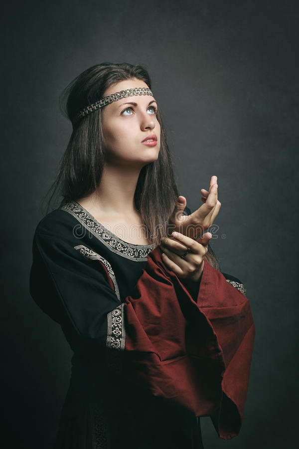 Bella donna nel pregare medievale del vestito immagine stock