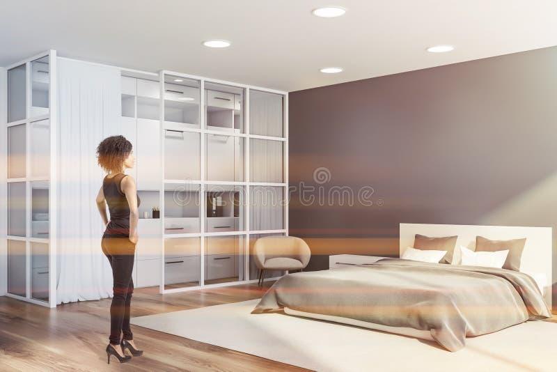 Bella donna nell'interno grigio della camera da letto immagine stock
