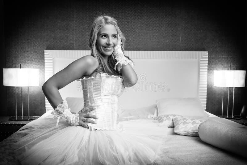 Bella donna nella camera da letto dell'hotel felice fotografia stock