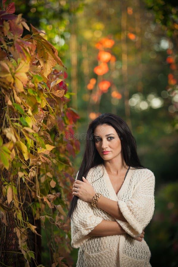 Bella donna nella posa bianca nel parco autunnale Giovane donna castana che spende tempo in autunno vicino ad un albero in forest fotografia stock libera da diritti