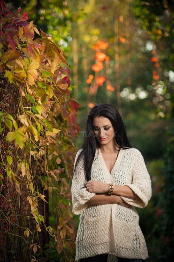 Bella donna nella posa bianca nel parco autunnale Giovane donna castana che spende tempo in autunno vicino ad un albero in forest immagini stock libere da diritti