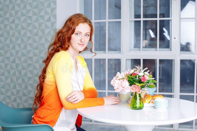 Bella donna nella sua scrittura della cucina su un taccuino a casa fotografie stock