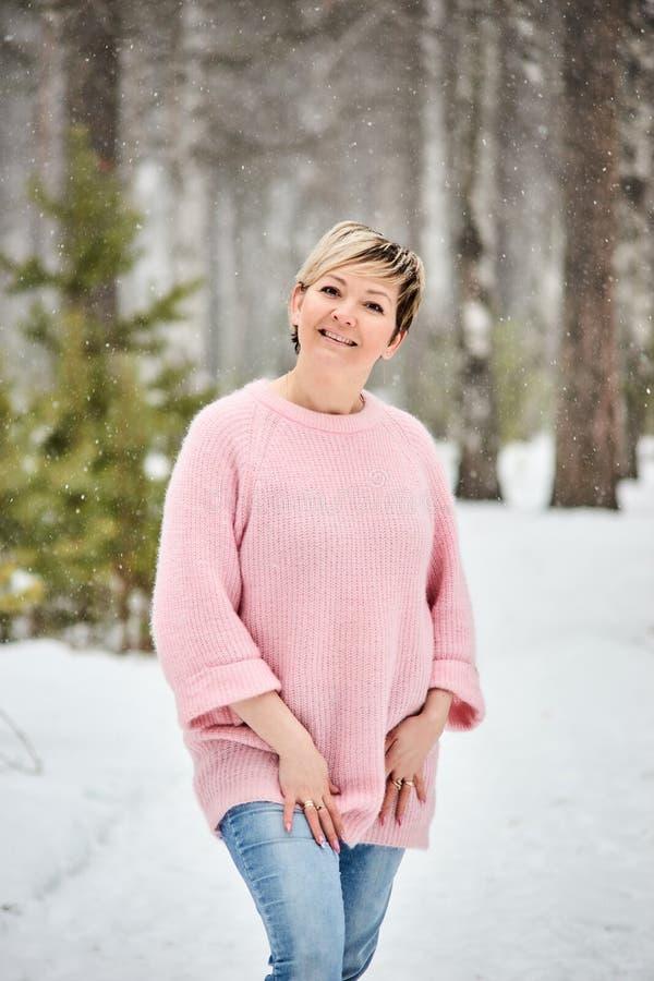Bella donna nelle precipitazioni nevose della foresta di inverno immagini stock libere da diritti