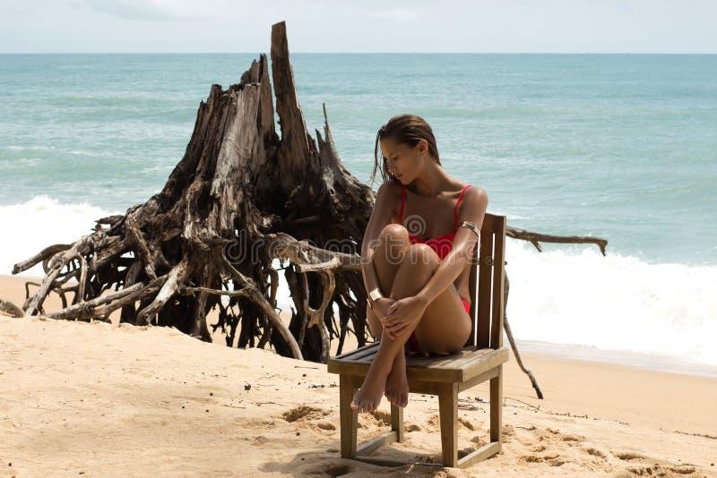 Bella donna in occhiali da sole e bikini rosso sulla spiaggia Sguardo di modo Signora sexy fotografie stock