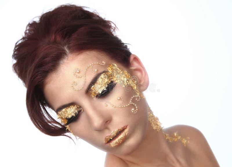 Bella donna ornata con i cosmetici della foglia di oro immagine stock libera da diritti