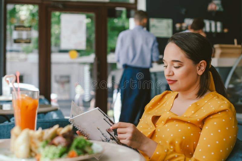 Bella donna più felice di dimensione che mangia insalata e che beve frullato sano in caffè fotografie stock