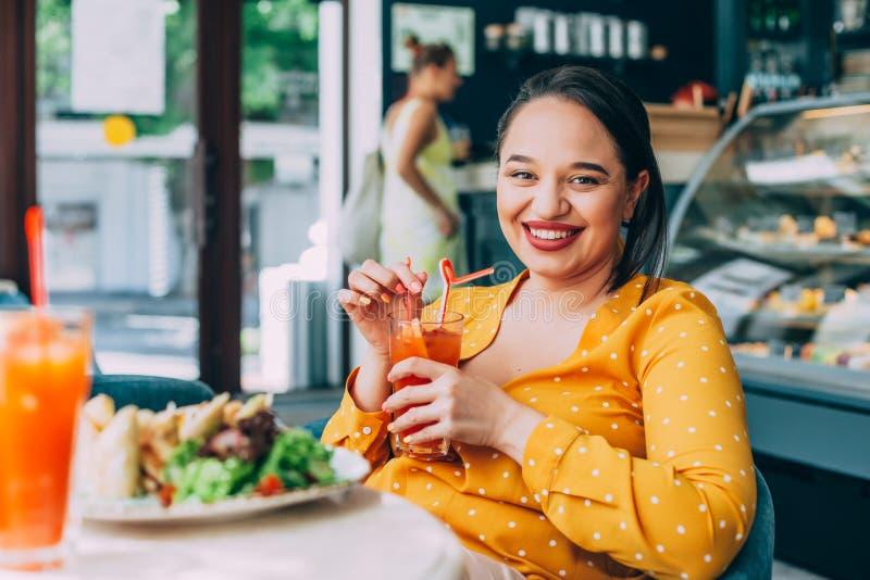 Bella donna più felice di dimensione che mangia insalata e che beve frullato sano in caffè fotografia stock libera da diritti