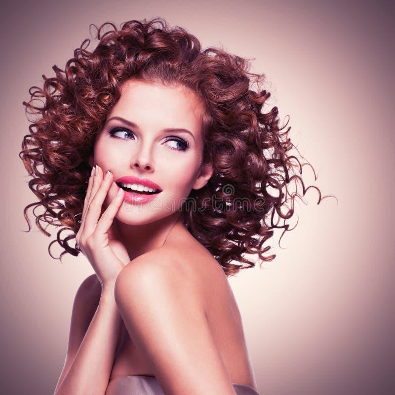 Bella donna premurosa sorridente con capelli ricci fotografia stock