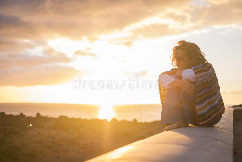 Bella donna riccia che si siede su una parete e godere della sensibilit? di tempo di tramonto la sensazione di libert? sulla sue  fotografia stock libera da diritti