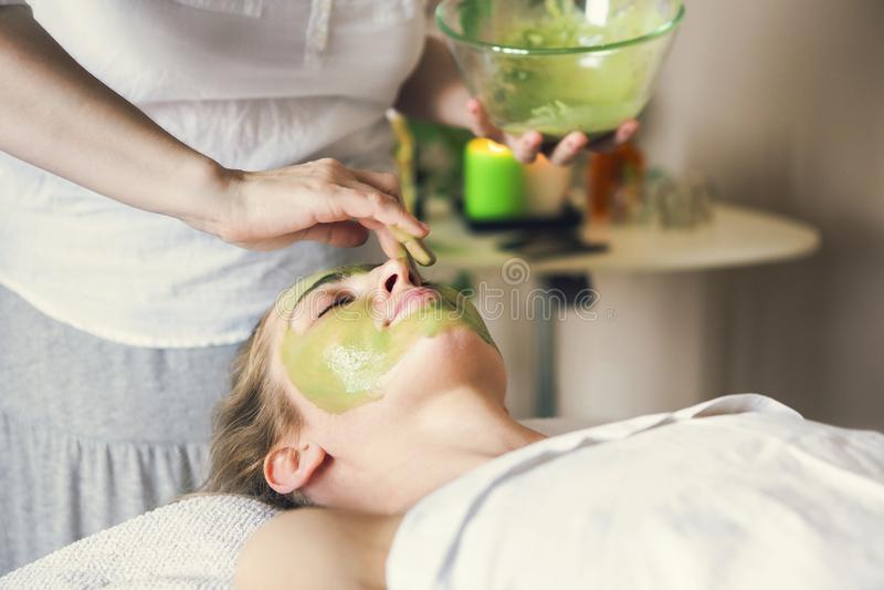 Bella donna rilassata che ha maschera di protezione dell'argilla nel salone della stazione termale immagine stock libera da diritti